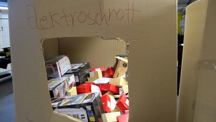 Neuware wird im Amazon-Lager in Winsen nahe Hamburg in Kartons gesammelt, um verschrottet zu werden. Die aussortierten Artikel, hier unter anderem Lichterketten, sind noch originalverpackt. Bildrechte: Greenpeace